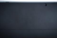 La parte posteriore del fondo con la macchina fotografica, sguardo moderno del nero della compressa immagini stock libere da diritti
