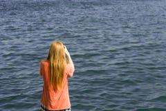La parte posteriore dell'uomo della testarossa prende le immagini dell'oceano Fotografia Stock
