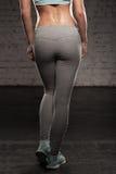 La parte posteriore delle donne su addestramento, ragazza di sport di forma fisica con l'ente muscolare, fa il suo allenamento Fotografia Stock Libera da Diritti