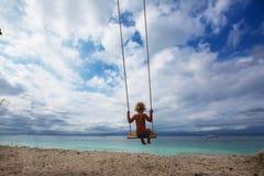 La parte posteriore delle oscillazioni dei ragazzi sta giocando sulla spiaggia fotografia stock libera da diritti