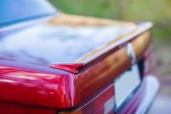 La parte posteriore di retro automobile rossa con una piccola ala immagini stock