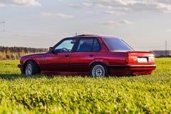 La parte posteriore di vecchia, automobile rossa e tedesca che sta sull'erba fotografie stock