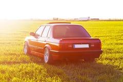 La parte posteriore di vecchia, automobile rossa e tedesca che sta sull'erba durante il tramonto fotografie stock libere da diritti