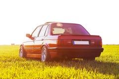 La parte posteriore di vecchia, automobile rossa e tedesca che sta sull'erba durante il tramonto immagine stock libera da diritti