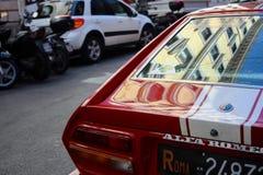 La parte posteriore rossa dell'automobile di Alfa Romeo ha messo a fuoco sull'angolo sinistro, ente riflettente del metallo, a Ro immagine stock
