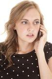 La parte superiore nera della donna punteggia il telefono serio Immagini Stock