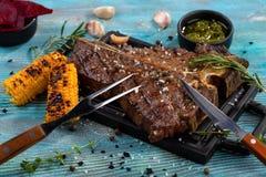 la participación de la carne de vaca del T-hueso sirvió en una tabla de cortar, visión desde arriba imagen de archivo libre de regalías