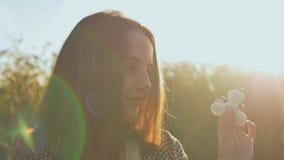 La participation de jeune fille et tourne dans les rayons du soleil de soirée des fileurs blancs et noirs de personne remuante de banque de vidéos