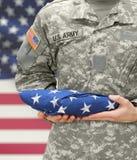 La participation de soldat de l'armée américaine a plié le drapeau des Etats-Unis avant son coffre Image stock