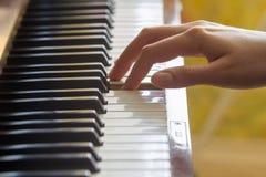 La participation du doigt de la main droite de la fille a appuyé sur la touche de note d'A sur un piano Photo libre de droits