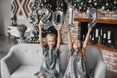 La participation heureuse de deux petites filles remet les ballons de nouvelle année, Numéro 2019 Se reposer sur le sofa dans la  photo libre de droits