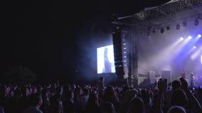 La partie de concert, admirateurs de foule sautent et ondulent des mains à l'événement de musique en direct de roche contre la sc banque de vidéos