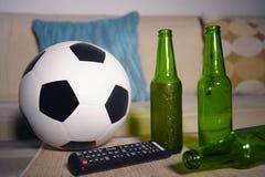 La partie de football de observation conceptuelle au sofa à la télévision avec des bouteilles à bière et le maïs éclaté roulent d Photos stock