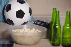 La partie de football de observation conceptuelle au sofa à la télévision avec des bouteilles à bière et le maïs éclaté roulent d Photographie stock