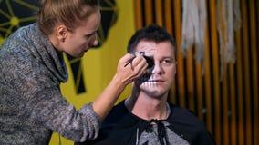 La partie de Halloween, artiste de maquillage dessine un maquillage terrible sur le visage d'un homme pour une partie de Hallowee banque de vidéos
