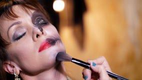 La partie de Halloween, plan rapproché, artiste de maquillage dessine un maquillage terrible sur le visage d'une femme de brune p banque de vidéos