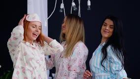 La partie de pyjama du ` s de femmes, trois beaux et les filles sexy rient et dansent sur le lit Célébrez la partie de poule banque de vidéos