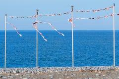 La partie ou la saison des vacances est sur- une plage vide de mer avec des piliers pour les drapeaux de fête Images stock