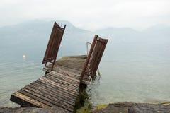 La pasarela raquítica en una orilla de un lago de la montaña Imagen de archivo