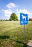 La passeggiata del cane firma dentro il parco Immagine Stock