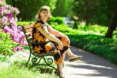 La passeggiata senior felice della donna nel bello giardino dell'estate e respira l'aria fresca fotografia stock