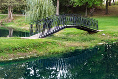 La passerella del giardino ha riflesso nell'acqua Immagine Stock