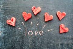 La pastèque a coupé en forme de coeur Amour d'inscription avec la craie Composition plate en configuration Concept de jour du ` s Photographie stock libre de droits