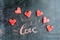 La pastèque a coupé en forme de coeur Amour d'inscription avec la craie Composition plate en configuration Concept de jour du ` s Photos stock