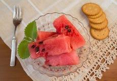 La pastèque coupe en tranches le dessert dans le bol en verre avec des biscuits Images libres de droits