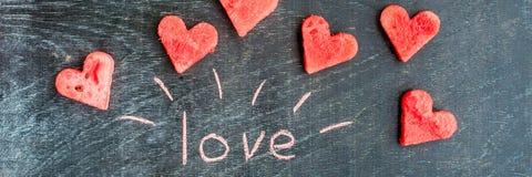 La pastèque de BANNIÈRE a coupé en forme de coeur Amour d'inscription avec la craie Composition plate en configuration Concept de Images stock