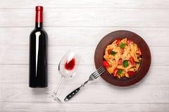 La pasta con formaggio, il pomodoro ciliegia, il bicchiere di vino e la bottiglia wine sui bordi di legno bianchi fotografia stock