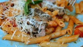 La pasta con salsa al pomodoro, carne, parmigiano ed i pomodori saporiti è mangiata con una forcella con il piatto blu archivi video