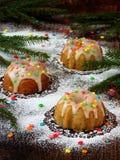 La pasta de azúcar adornada los molletes dulces, multicolora asperja Magdalenas en fondo oscuro con las ramas spruce La Navidad y Foto de archivo libre de regalías