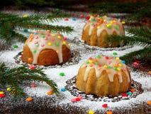 La pasta de azúcar adornada los molletes dulces, multicolora asperja Magdalenas en fondo oscuro con las ramas spruce La Navidad y Imágenes de archivo libres de regalías