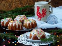La pasta de azúcar adornada los molletes dulces, multicolora asperja Magdalenas en fondo oscuro con las ramas spruce La Navidad y Fotografía de archivo
