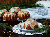 La pasta de azúcar adornada los molletes dulces, multicolora asperja Magdalenas en fondo oscuro con las ramas spruce La Navidad y Fotos de archivo