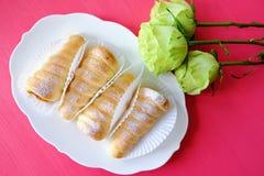 La pasta de hojaldre rueda tartas y rosas de las natillas fotos de archivo