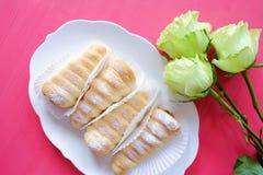 La pasta de hojaldre rueda tartas y rosas de las natillas fotografía de archivo