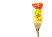 La pasta degli spaghetti con basilico e un ramoscello di pianta feriscono su una forcella con un pezzo di pomodori ciliegia isola Fotografie Stock Libere da Diritti