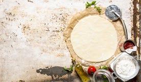 La pasta desarrollada de la pizza con la salsa de la harina y de tomate foto de archivo