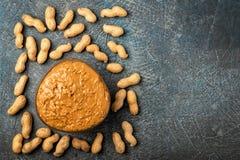 La pasta di arachidi in barattolo aperto ed arachidi nella buccia ha sparso sulla tavola immagine stock libera da diritti