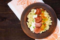 La pasta di Galetti con i pezzi di salsiccia, i pomodori gialli e la salsa di senape cremosa in un'argilla lanciano Immagine Stock