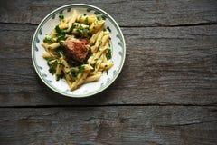 La pasta di Penne in salsa al pomodoro con il pollo, pomodori ha decorato il prezzemolo Fotografie Stock