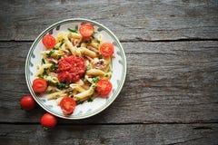La pasta di Penne in salsa al pomodoro con il pollo, pomodori ha decorato il prezzemolo Fotografie Stock Libere da Diritti