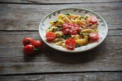 La pasta di Penne in salsa al pomodoro con il pollo, pomodori ha decorato il prezzemolo Immagine Stock