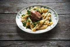 La pasta di Penne in salsa al pomodoro con il pollo, pomodori ha decorato il prezzemolo Immagini Stock