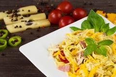 La pasta di tagliatelle con la salsa di pesto, il bacon, il formaggio di Gauda, del cheddar, dell'emmental ed il basilico lascia  immagini stock libere da diritti