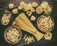 La pasta differente scrive dentro i cucchiai di legno sulla tavola Fotografia Stock Libera da Diritti