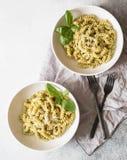 La pasta italiana con la salsa di pesto, il basilico fresco ed il parmigiano in un bianco lancia su fondo grigio Fa fronte lo spa immagine stock libera da diritti