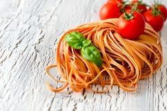 La pasta italiana rossa cruda con il basi e il tomatoesl copiano lo spazio Immagine Stock